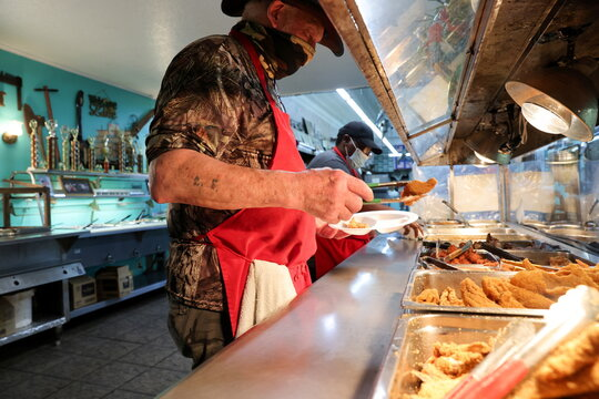 A worker assembles a dinner plate along the buffet line at Pap's Place catfish restaurant in Ackerman, Mississippi