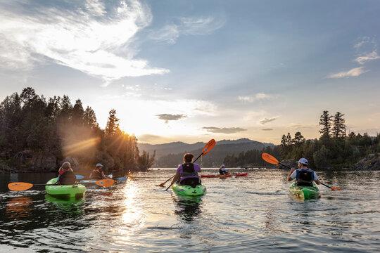 Family sea kayaking on Flathead Lake in Somers, Montana, USA