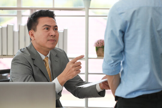 Executive boss Asian businessman in suit holding paperwork and blaming young employee with anger and serious gesture look like he comments as disagree or unacceptable for his project work