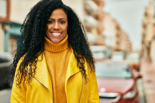 Middle age african american woman smiling happy standing at the city.