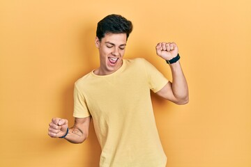 Young hispanic man wearing casual yellow t shirt dancing happy and cheerful, smiling moving casual and confident listening to music