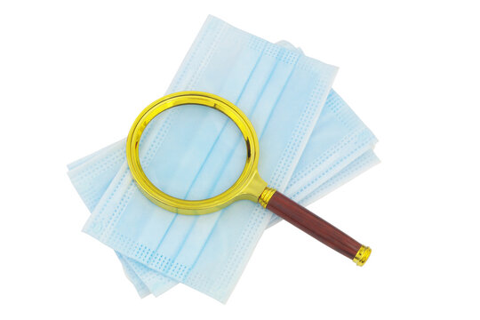 Magnifying glass on protective medical face masks isolated on white background
