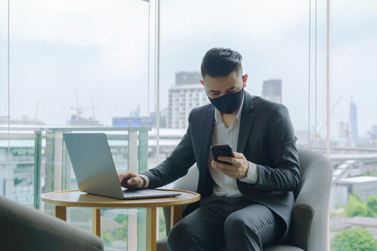 Portrait of young Asian businessman person wearing a face mask, texting a mobile phone and computer laptop notebook in technology device in office with urban city view. People lifestyle.