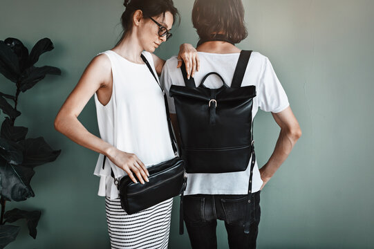 Street style concept. Beautiful girl with a boyfriend presenting designer leather bags. Backpack For Men, Black Leather Belt Bag, Large Waist Bag.