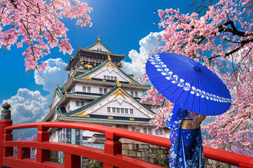 Wall Mural - Asian woman wearing japanese traditional kimono looking at cherry blossoms and castle in Osaka, Japan.