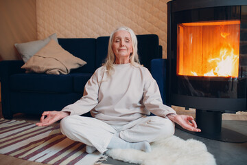 Portrait of senior woman sitting in lotus position indoors with fireplace. Yoga and meditation zen like concept.