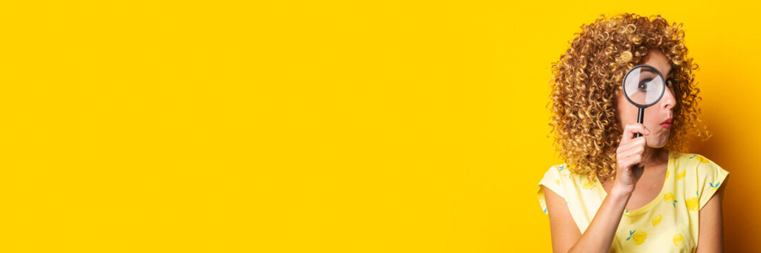 surprised curly young woman looks through a magnifying glass on a yellow background. Banner.