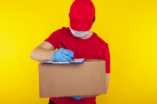 Delivery man holding cardboard boxes in medical rubber gloves and mask. copy space. Fast and free Delivery transport . Online shopping and Express delivery . Quarantine .