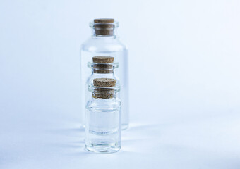 Glass pharmacy bottles with liquid on blue background.