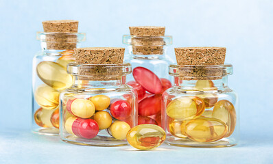 Glass pharmacy bottles with red and yellow pills on blue background.