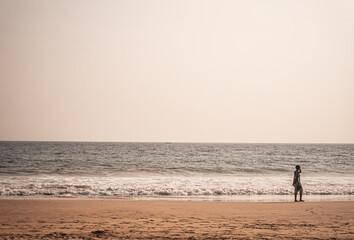Człowiek idący brzegiem morza, na tle plaży i oceanu.