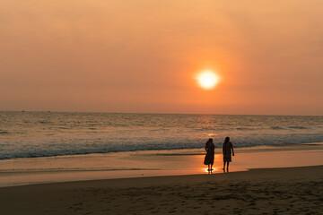 Kobiety spacerujące brzegiem oceanu o zachodzie słońca, ciemno pomarańczowy nastrojowy...