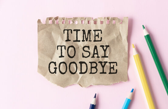 TIME TO SAY GOODBYE is written on a notepad on an office desk with pencils.