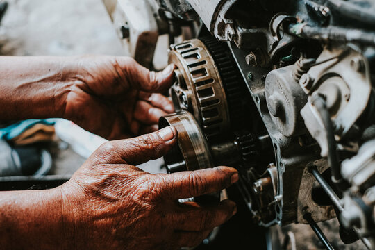 Motorcycle mechanics are assembling the motorcycle engine clutch assembly and maintenance.