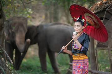 Beautiful Asian Woman wears thai dress with her elephant. Wall mural