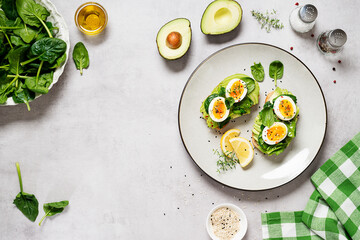 Healthy toast with sliced avocado, boiled eggs, spices and fresh spinach. Delicious breakfast or snack on gray stone background. top view, space for text