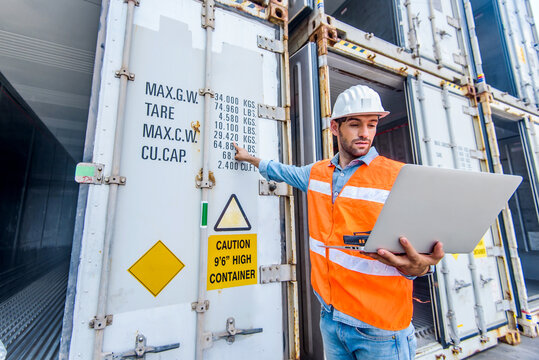 Confident man engineer wearing white safety helmet using computer laptop and check for control loading containers box from Cargo freight ship for import and export, transport