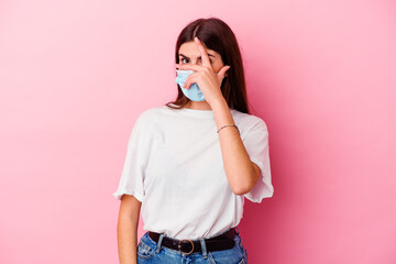 Young caucasian woman wearing a mask for virus isolated on pink background blink through fingers...