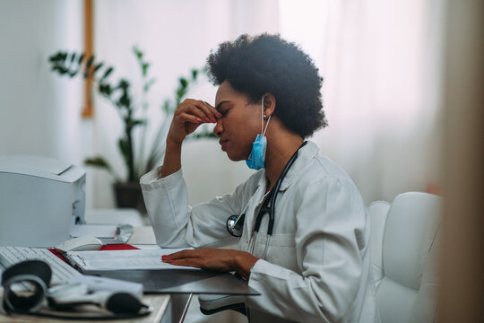 Tired female doctor using laptop at doctor's office