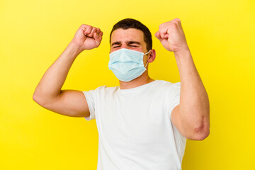 Young caucasian man wearing a protection for coronavirus isolated on yellow background celebrating...