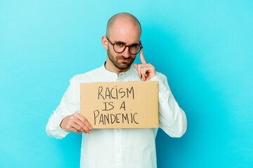 Young caucasian bald man holding a racism is a pandemic isolated on white background pointing...