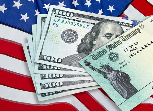 United States Treasury check with US currency dollar bills on American flag. Coronavirus economic impact stimulus payments or IRS tax refund.