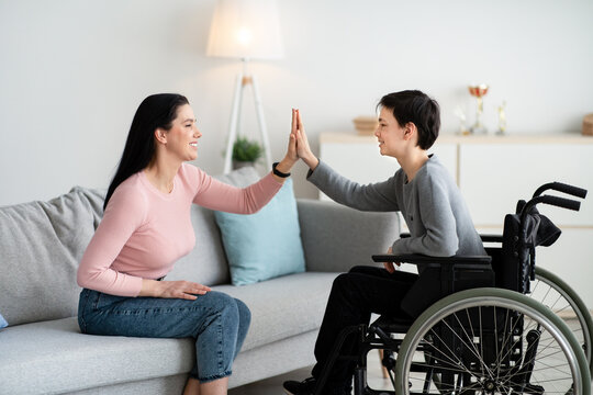 Happy teenage boy in wheelchair high fiving his mother at home, side view