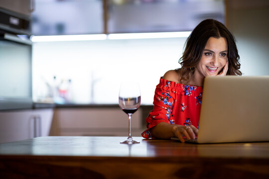 Pretty, mid-aged woman having a virtual Wine Tasting Dinner Event Online Using Laptop with friends