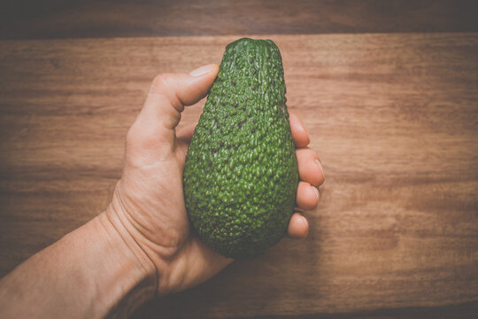 Close-up of a hand holding an avocado - locally sourced, organic food