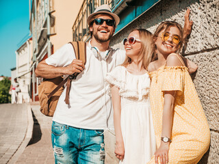 Group of young three stylish friends posing in the street. Fashion man and two cute female dressed...