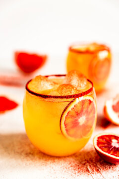 Blood orange margarita cocktail in an old fashioned glass with smoked paprika on the rim, pink grapefruit. High key light and bright photo.