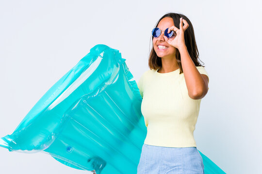 Young mixed race woman holding an air matress excited keeping ok gesture on eye.