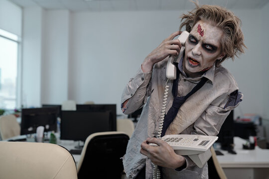Zombie businessman with phone receiver by ear standing by workplace in front of camera