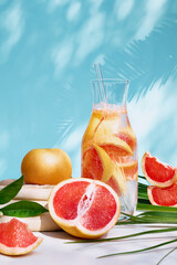 Summer cocktail with grapefruit and rosemary and juicy slices citrus fruits. Fresh healthy grapefruit beverage on sunlight with shadows. Creative drink on blue pastel background.