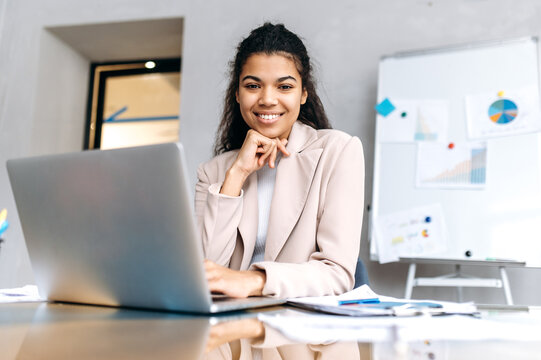Attractive female employee is sitting at the desk, smiling and looking at the camera. Beautiful african american businesswoman using laptop, working on project or distantly studying