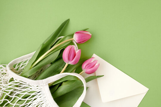 spring flat lay with string bag isolated on green background