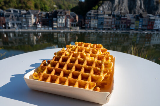 Sweet fresh baked Belgian waffles served outdoor with view on Maas river in Dinant, Wallonia, Belgium.