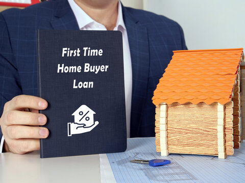 Young woman holding a blank card in hands. Conceptual photo about First Time Home Buyer Loan with written text.