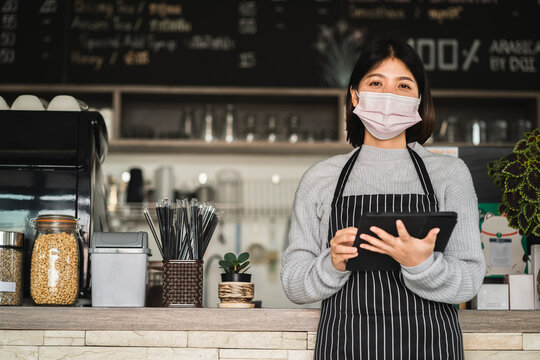 portrait view of young women entrepreneur coffee shop wearing face mask standing in front of counter with tablet in cafe.