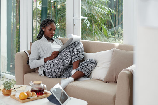Concentrated Black young woman in loungewear working from home, she is sitting on sofa and reading business document