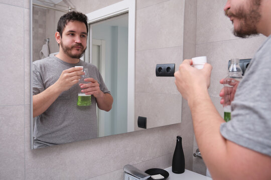 Man rinsing mouth with green mouthwash in bathroom. Teeth care concept.
