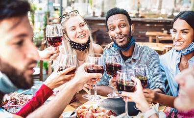 Fototapeta Multiracial people toasting wine at restaurant garden wearing open face mask - New normal lifestyle concept about happy friends having fun together - Bright filter with focus on guy looking at camera