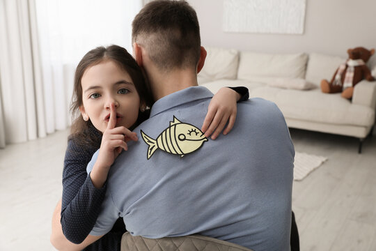 Cute little girl sticking paper fish to father's back at home