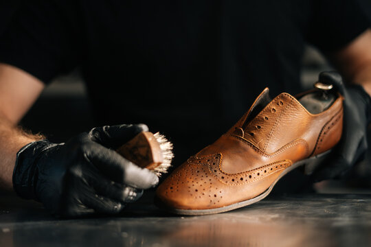 Close-up front view of unrecognizable shoemaker cleaning with brush old light brown leather shoe. Concept of cobbler artisan repairing and restoration work in shoe repair shop.