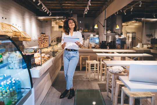 Professional Caucaisan sales representative working in small local bakery checking report for delivery order, full length portrait of self employed woman accounting in grocery service industry