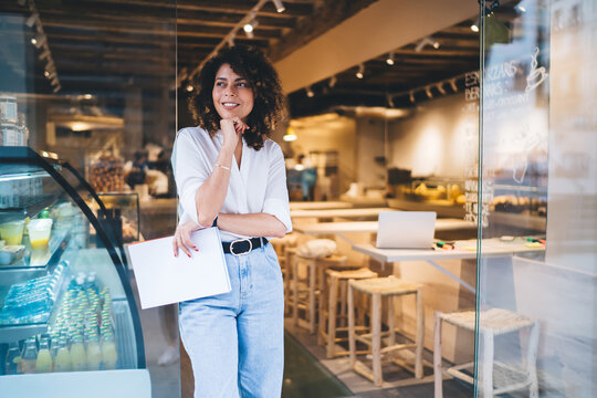 Happy female manager with menu in hand standing in doorway of local cafeteria and smiling, pretty Caucaisan small owner enjoying business lifestyle for working with franchise takeaway industry