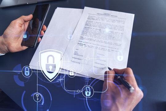 A businessman in formal wear signing the contract to prevent probability of risks in cyber security. Padlock Hologram icons over the working desk.