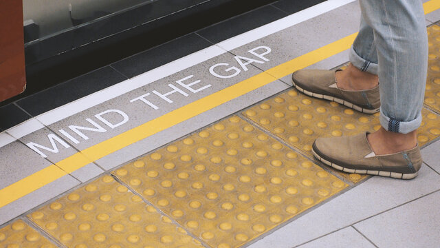 Mind the gap sign. text on train station platform. white text signal on metro or underground floor. Yellow line train station. london england europe old transport platform. Mind the gap for safety.