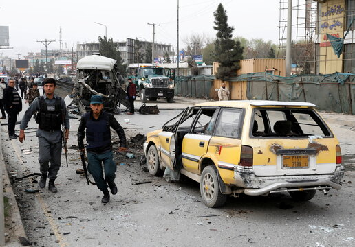 Afghan police officers inspect the site of a minibus blast in Kabul