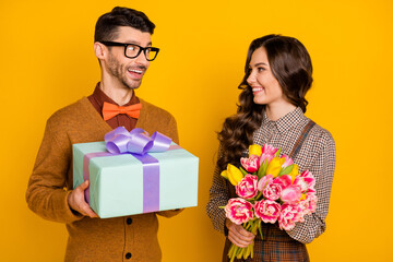 Photo of brown haired attractive couple give gift box hold flowers anniversary isolated on yellow color background Wall mural